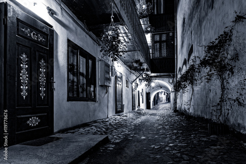 Moody monochrome view of a cobblestone street passage in the old city center of Sibiu, Romania