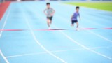 Slow motion selective focus at young Asian boy running on blue track to the finished line.