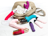 Many watches female vibrators with a bag on white background
