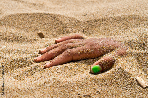 Poster hand in rigor mortis on the beach