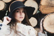 Gorgeous young woman in autumn outfit posing next to tree chunks