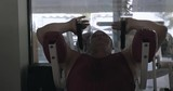 Middle-aged man making abdominal exercises with simulator in gym front view of doing press fitness exercises on machine