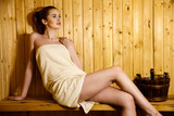 Beautiful red-haired young woman relaxing in a finnish sauna