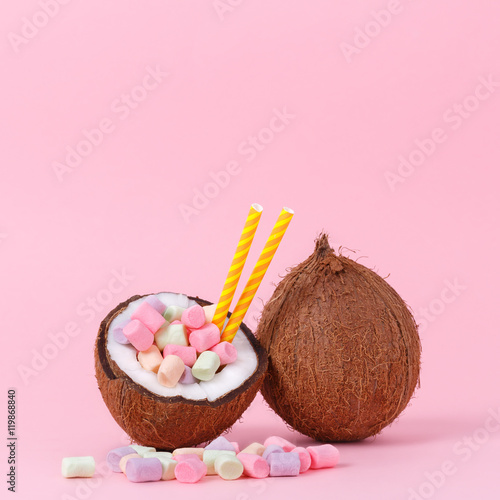 Fotobehang Purper Marshmallow in half coconut on a pink background. Minimal concept