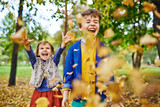 Two children, boy and younger girl, playing in autumn park, laughing and screaming as they throw fallen golden leaves up around, enjoying warm September day