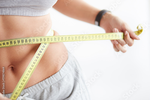 Leinwanddruck Bild Slim young woman measuring her thin waist with a tape measure close up