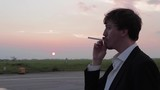 Businessman in Black Suit Smokes an Electronic Cigarette at the Sunset and Laughs