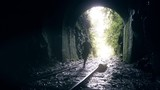Woman running away of the darkness over the rails of an abandoned train in a dark tunnel