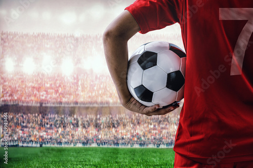 Poster soccer football player in red team concept holding soccer ball in the stadium
