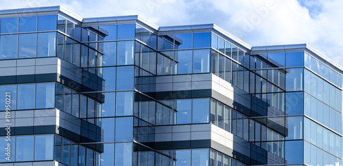 Lines, glass and reflections of modern architecture.  Glass panelled building of new office space in Moncton, New Brunswick.   New commercial real estate in the city.