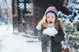 happy child girl playing with snow on snowy winter walk on backyard, making snowballs in the garden