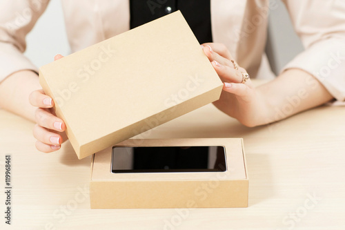 Woman opening box with new smartphone, close-up Poster