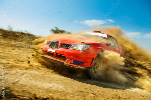 Plakat Powerful red rally car in the drift on dirt road