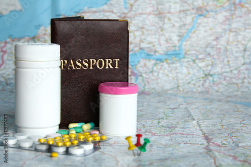 Tablets, passport on map background. Medical tourism concept. Poster