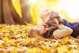 Mutter mit Tochter liegen im Laub