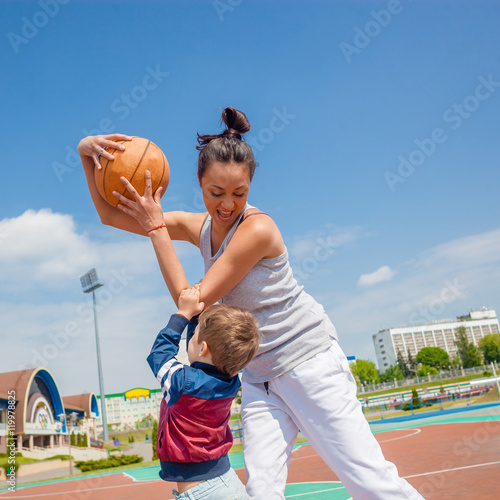 Mom and little boy son playing basketball Poster