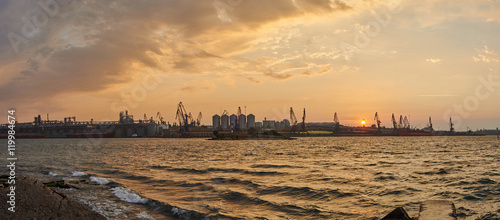 Foto op Canvas Zee zonsondergang Cargo warehouses in the seaport in sunrise