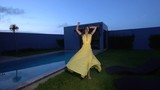 Gorgeous fashion woman with dark hair in elegant yellow dress posing and dancing beside swimming pool at luxurious villa - video in slow motion