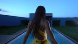 Gorgeous fashion woman with dark hair in elegant yellow dress smiling and dancing beside swimming pool at luxurious villa - video in slow motion