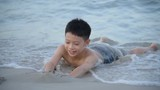 Asian boy playing at the beach