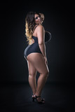 Young beautiful caucasian plus size model in swimsuit, xxl woman on black background