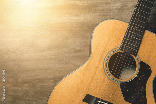 Acoustic guitar on vintage wooden background with sunlight effect filter Poster