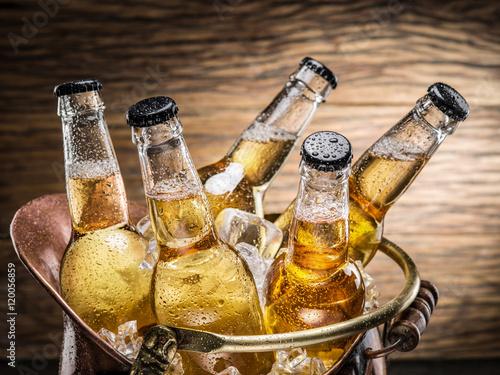 Cold bottles of beer in the brazen bucket. Poster