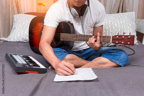 Póster asian male composer, musician writing song & playing guitar on bed