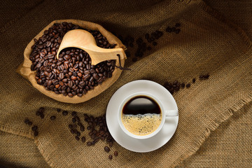 Top view of cup of coffee and coffee beans on burlap background © amenic181