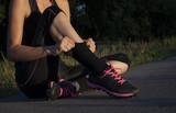mooie jonge vrouw haalt sokken op als voorbereiding op hardlopen