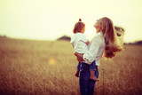 warm portrait of mother and daughter in country style in the field