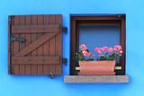 Finestra il legno con fiori sul davanzale in una tipica casa Alsaziana con la facciata blu
