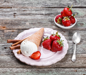 Ice cream with fresh strawberries and jam in waffle cone on plate, on rustic wooden background