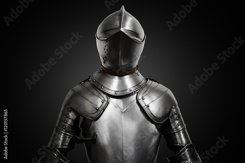 Old metal knight armour on black background Poster
