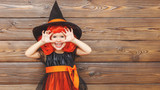 funny child girl in witch costume for Halloween scares
