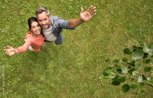 Top view. couple standing in the grass looking at the camera
