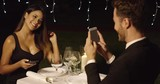 Man in suit takes photo of beautiful dinner date from across the table while dining at night