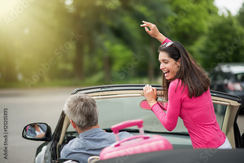 cheerful couple going on a road trip in their convertible car Poster