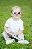 Portrait of funny cute adorable smiling laughing white Caucasian toddler child boy with blond hair in white t-shirt and sunglasses sitting on green grass holding a book.