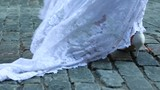 Bottom of brides dress as she stands in street on a windy day