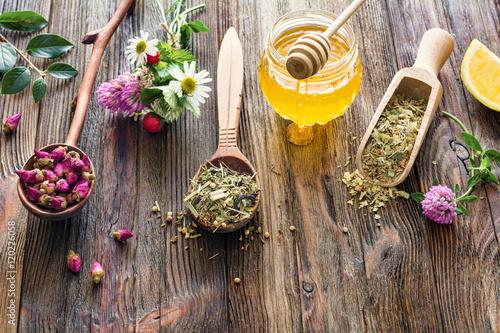 Assortment of dry herbal tea in wooden spoons, jar of honey, fresh flowers