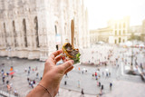 Holding delicious snack with anchovy on the Duomo background in Milan