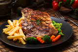 Grilled beef steak served with French fries and vegetables on a