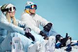 Young couple wearing sports clothing and ski goggles looking at something