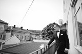 Fashionable model groom standing on the balcony leaning on railing, B&W photo