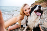 Cheerful woman taking selfie with dog on the beach