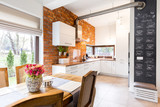 Spacious kitchen with white furniture and brick wall