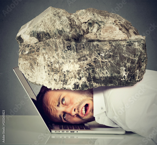 Stressed business man with head squeezed between laptop and rock Poster