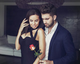 Sexy young romantic man gives rose to stylish woman