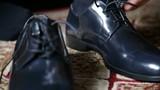 Dettaglio di un uomo che si sta allacciando scarpe nere prima del suo appuntamento